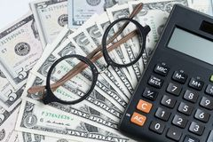 Selective focus on glasses on pile of dollar banknotes and calcu Stock Image
