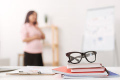 Selective focus of glasses with pregnant woman talking on phone. Everyday work. Selective focus og glasses lying on the table in the office while pregnant woman royalty free stock images
