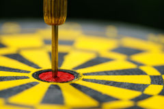 Selective focus on gold needle dart in the center of dartboard a Royalty Free Stock Photo