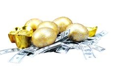 Selective focus golden eggs on artificial US dollars stock images