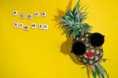 Fresh Pineapple wears sunglasses and red lips with aloha summer word written on wooden block on yellow background. Tropical summer concept stock photos