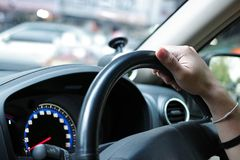 Selective focus on hand of driver on steering wheel of car.  Stock Photo