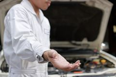 Selective focus on hand of mechanic proposes partnership and offering for handshake. Auto repair service. Stock Photography