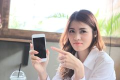 Selective focus on hands of attractive young Asian woman pointing finger on mobile smart phone screen in modern room background. Selective focus on hands of Stock Images