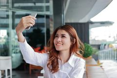 Selective focus on hands of attractive young Asian woman taking photo or selfie on mobile smart phone in office. Shallow depth of Royalty Free Stock Photography