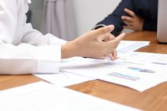 Selective focus on hands of business people discussing charts between meeting in conference room Royalty Free Stock Photos