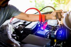 Selective focus hands do charging car battery with electricity through cables from from other car royalty free stock photo