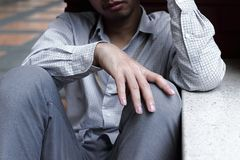 Selective focus on hands of Frustrated stressed young Asian business man sitting on the floor Royalty Free Stock Image