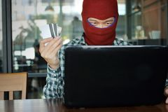 Selective focus on hands of Masked hacker wearing a balaclava holding credit card between stealing data from laptop. Internet crim. E concept Royalty Free Stock Photo