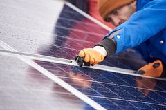 Professional electrician worker installing solar panels. Selective focus on the hands of a professional male electrician installing solar panels working on Stock Image