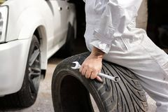 Selective focus on hands of professional mechanic in uniform sitting on tire and holding wrench at the repair garage background. Royalty Free Stock Photo