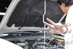 Selective focus on hands of professional young mechanic man raising two fingers up it is shows fight with job against car in open Stock Image