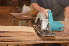 Selective focus on hands of senior carpenter cutting a piece of wood with electric circular saw in carpentry workshop Stock Image