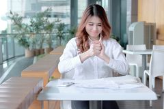 Selective focus on hands of young Asian employee holding crumpled paper and feeling stress against her job in office. Selective focus on hands of young Asian Stock Photo