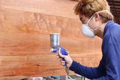 Selective focus on hands of young Asian worker with safety mask painting a piece of wood with spray gun in home workshop. Shallow. Depth of field Royalty Free Stock Photos
