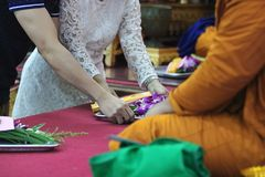 Selective focus on hands of young couple make merit to monks in buddhism temple Royalty Free Stock Photos