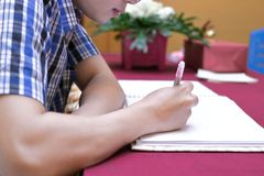 Selective focus on hands of young guest man writing on memory book for blessing word to newlyweds couple in wedding ceremony Royalty Free Stock Photos