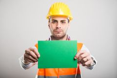 Selective focus of handsome architect holding green cardboard. On gray background with copyspace advertising area royalty free stock photos