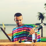 Selective focus on handsome Mexican bartender in colorful poncho. Standing on the bar counter on the beach and adding some liquid in a cup. Concept of Stock Photos