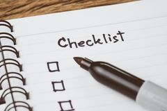Selective focus on handwriting headline the word Checklist with black marker pen and check box on small notepad on wood table, to. Do list, prioritize or royalty free stock photo