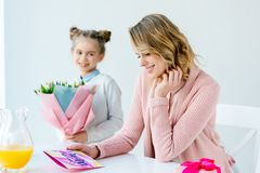 Selective focus of happy mother looking at greeting postcard and daughter with bouquet of flowers standing near by, mothers. Day concept royalty free stock photos
