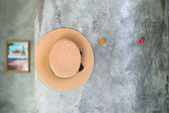 Selective focus of hat hanging on the cement textured wall. Imply to relax and vacation Royalty Free Stock Photos