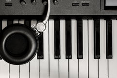 Selective focus headphone on key piano background. Royalty Free Stock Photography