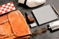 Selective focus on holiday set of a traveler - sunglasses, notebook, pen, leather bag, pipe, chessboard Stock Image