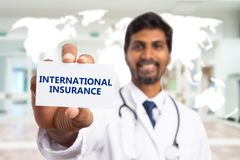 Selective focus image of doctor presenting international insurance. Selective focus close-up image of indian male doctor presenting international insurance white royalty free stock photos