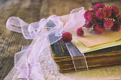 Selective focus image of dry flowers and old vintage books on wooden table. retro filtered image Stock Photo
