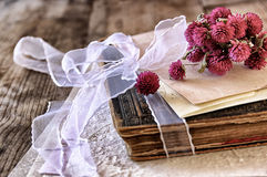 Selective focus image of dry flowers and old vintage books on wooden table. retro filtered image Stock Photos
