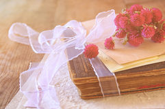 Selective focus image of dry flowers and old vintage books on wooden table. retro filtered image Stock Photography