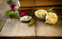 Selective focus image of dry rose, antique necklace and old vintage books on wooden table. retro filtered image Stock Photos