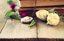 Selective focus image of dry rose, antique necklace and old vintage books on wooden table. retro filtered image Royalty Free Stock Photo