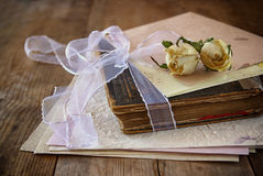 Selective focus image of dry rose and old vintage books on wooden table. retro filtered image Royalty Free Stock Photo