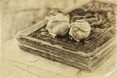 Selective focus image of dry rose and old vintage books on wooden table. retro filtered image Royalty Free Stock Photography