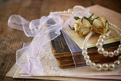 Selective focus image of dry roses, white pearls necklace and old vintage books on wooden table. retro filtered image Royalty Free Stock Image