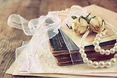 Selective focus image of dry roses, white pearls necklace and old vintage books on wooden table. retro filtered image Royalty Free Stock Photos
