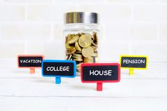 Saving types. Selective focus of jar of gold coins with four blackboard written with & x27;VACATION& x27;,& x27;COLLEGE& x27;,& x27;HOUSE& x27; and & x27;PENSION royalty free stock photos