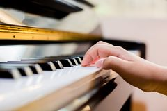 Selective focus of kid fingers and piano key to play the piano with lighting. There are musical instrument for concert or learning music stock image