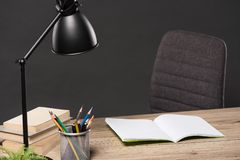 Selective focus of lamp, colour pencils, stack of books, plant and empty textbook on table. On grey background royalty free stock image