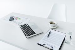 Selective focus of laptop, cup of coffee and contract at workplace. Isolated on white Royalty Free Stock Images