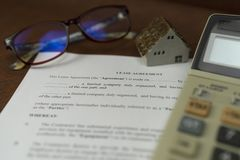 Selective focus of lease agreement with ceramic home and calculate royalty free stock photo