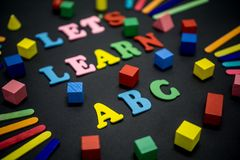 Colorful Let`s Learn ABC. Selective focus of Let`s Let ABC text title on black background Royalty Free Stock Images