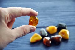 Polished amber stone in the fingers stock photos