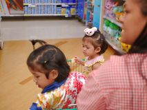 Little Asian baby girl  furthest  looking and standing in a shopping cart with her sister while her mother stock images