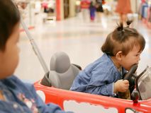 Little Asian baby girl, 17 months old, right biting a steering wheel of a mini car - toddlers and biting royalty free stock image