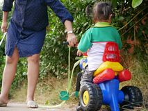 Little Asian baby girl receiving help from her mother when she could not properly control a bicycle, while learning to ride it royalty free stock photos