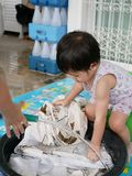 Little Asian baby girl right, washing clothes at home. Selective focus of a little Asian baby girl right, together with her sister, washing clothes at home royalty free stock photos