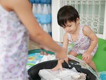 Little Asian baby girl right, washing clothes at home. Selective focus of a little Asian baby girl right, together with her sister, washing clothes at home royalty free stock image